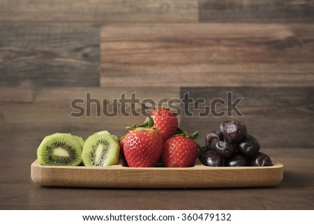 Strawberries, Kiwi and Dates in a Bamboo Plateau. Fresh fruits and dried fruit platter. Fruit Salad. - stock photo