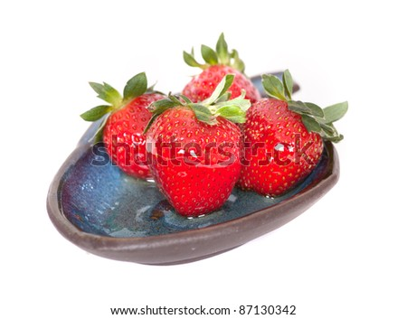 Strawberries on a ceramic plate dripping with honey - stock photo