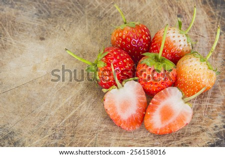 strawberries on old wooden textured table in natural background - stock photo