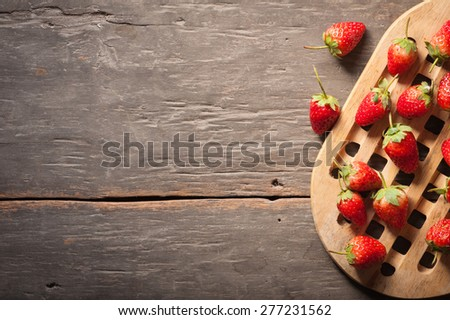 Strawberries on wood background in vintage style with low key scene. - stock photo