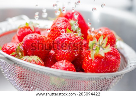 Strawberries rinsed with water - stock photo