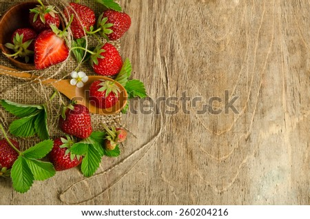 Strawberries with leaves on wooden background from left side - stock photo