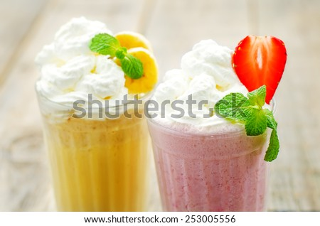 strawberry and banana milkshake with whipped cream on a blue background. tinting. selective focus - stock photo