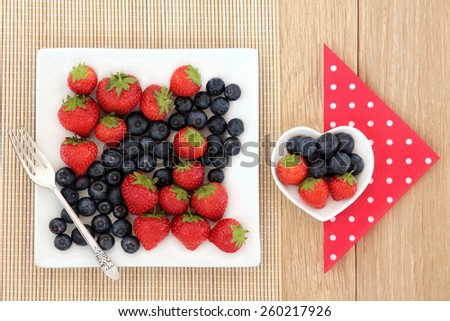 Strawberry and blueberry fruit in square and heart shaped porcelain dishes with polka dot napkin and old silver fork over oak and bamboo.