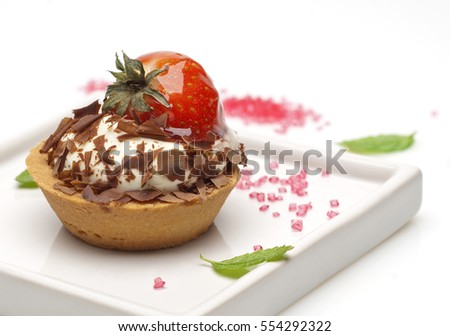 strawberry and cream tartlet with chocolate flakes on a white modern plate