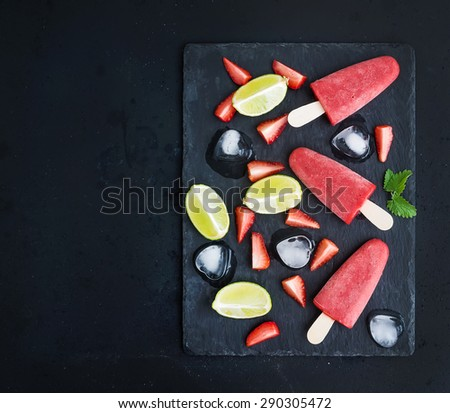Strawberry and lime ice-creams or popsicles with fresh cut berries and citruses, ice cubes and melissa leaves on black slate tray over dark grunge backdrop, top view, copy space - stock photo