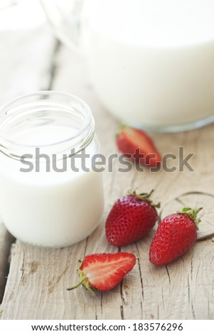 Strawberry and milk on wooden background