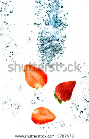 Strawberry are falling in water with a big splash - stock photo