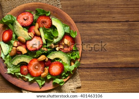 Strawberry, avocado, lettuce salad with cashew nuts on plate, photographed overhead on dark wood with natural light - stock photo