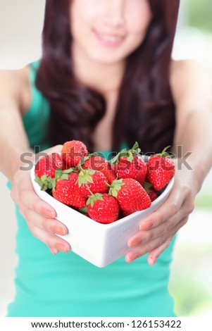 Strawberry - beautiful woman showing fresh strawberries with nature green background, focus on fruit, asian beauty mode