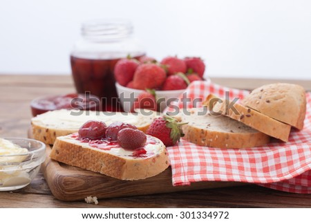 Strawberry berries, Strawberry jam, butter and bread on wooden table. Breakfast with fruits horizontally. Overhead view on healthy breakfast with strawberry jam. Macro shot selective focus - stock photo