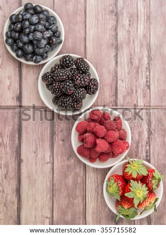 Strawberry, blackberry, raspberry and blueberry fruits in white bowl over wooden background