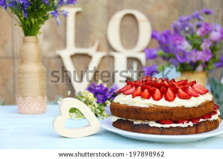 Strawberry cake with wildflowers and decorative letters on table  - stock photo