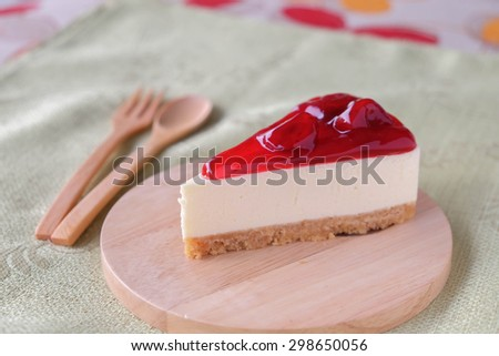 Strawberry cheese cake on wood plate - stock photo