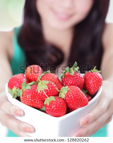 Strawberry - close up of beautiful woman showing fresh strawberries, asian beauty model - stock photo