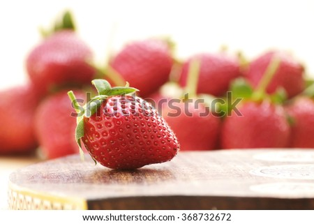 Strawberry close-up with stack of strawberries as blur background