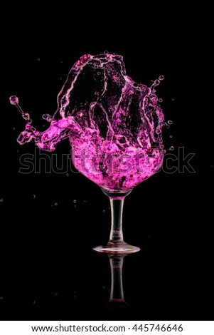 strawberry cocktail splash out of glass on black background. - stock photo