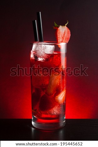 Strawberry cocktail with ice on black table and a red gradient background - stock photo