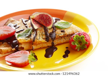 Strawberry crepes with chocolate syrup and figs over white closeup