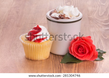 Strawberry cupcake with a cup of hot chocolate and a bright red rose on dark wooden tabletop - anniversary or Valentine's treat to a loved one - stock photo