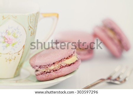 Strawberry flavored macarons with an antique tea cup and saucer. Extreme shallow depth of field with selective focus on macaron in the foreground. - stock photo