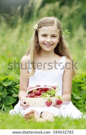 Strawberry, fruit garden - young girl with picked strawberries in the garden - stock photo