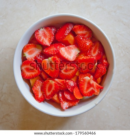 Strawberry halves in a white bowl on a marble