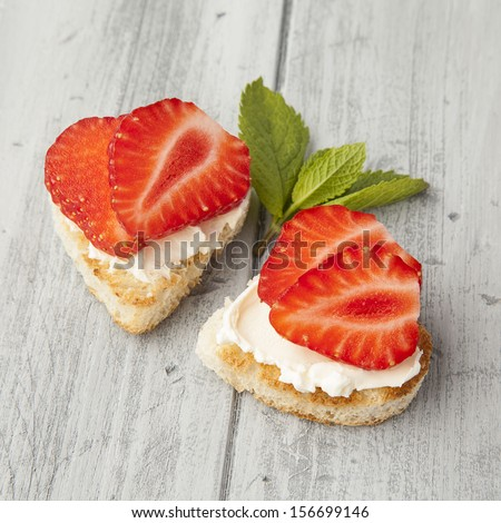Strawberry heart-shaped toasts with mint leafs  - stock photo