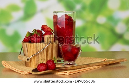 Strawberry in a bucket and in a glass, berries in a bowl and a spoon, napkins on a table