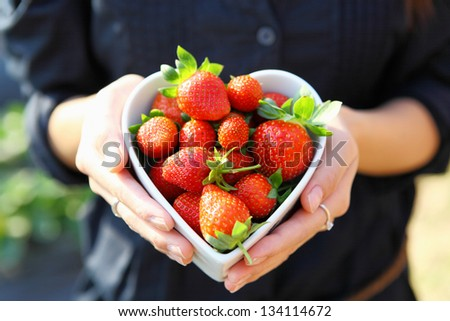 strawberry in heart shape bowl with hand - stock photo