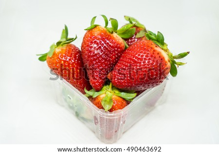 Strawberry in plastic packaging on white background