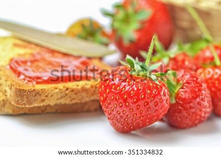 Strawberry jam and fresh strawberries on white background - stock photo
