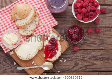 Strawberry jam, butter and bread on wooden table. Breakfast with strawberry jam top view horizontally. Macro shot selective focus - stock photo