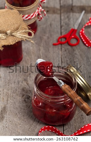 Strawberry Jam on old wooden background. Selective focus.