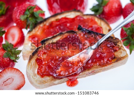 Strawberry jam on slices of toast with strawberries