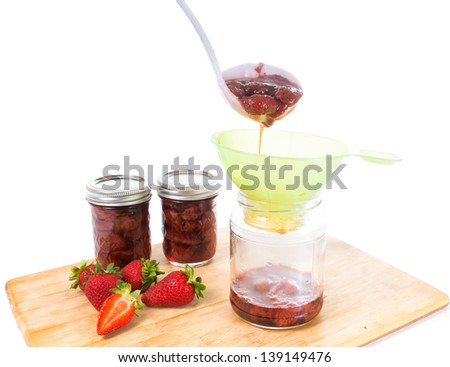 Strawberry jam spreads on banks - stock photo