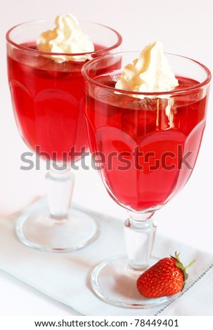 Strawberry jelly with fresh strawberry and cream in tall glass on white background