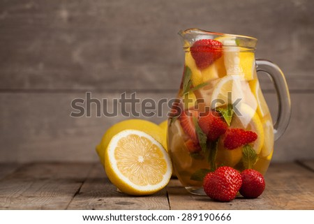 Strawberry lemonade with lemon on wooden table. Selective focus. - stock photo