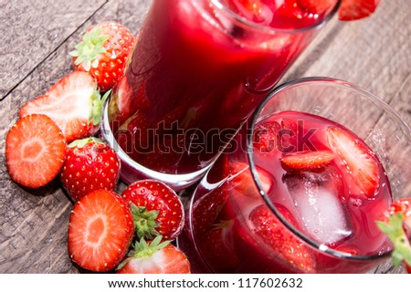Strawberry Liqueur with fresh fruits on wooden background - stock photo