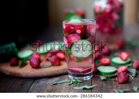 strawberry mint cucumber infused water decorated in rustic style on dark wood table background - stock photo