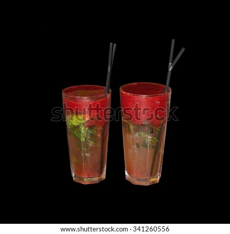 Strawberry mojitos, red and green alcoholic drinks with ice and gray straws isolated on black.