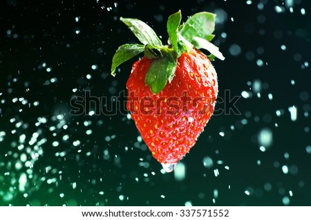 Strawberry on a green background with drops of water - stock photo