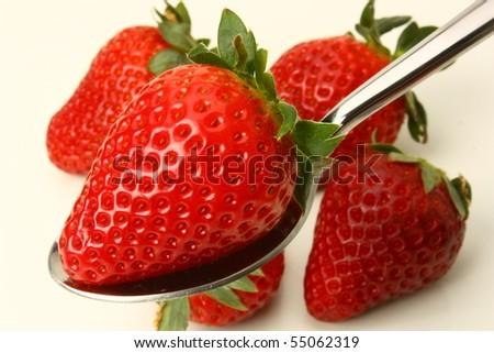 Strawberry on a spoon and strawberry background - stock photo