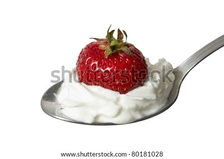 Strawberry on a spoon with whipped cream. Isolated with clipping path.