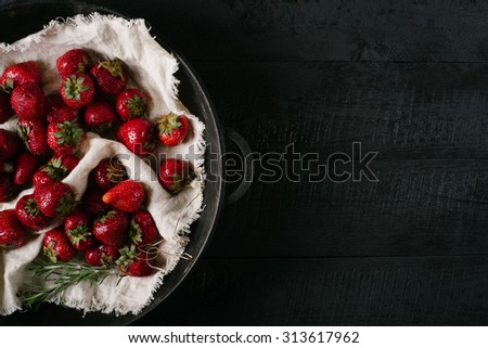 Strawberry on light textiles in a round metal bowl on a black wooden background - stock photo