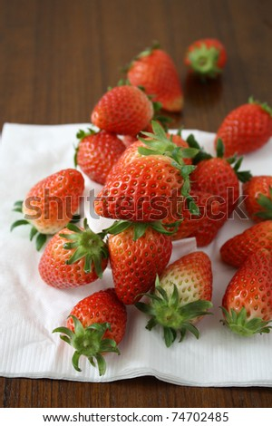 strawberry on white paper napkin, on wooden surface