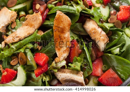 Strawberry Orange Honey Balsamic Salad on spring baby greens and spinach top view macro shot