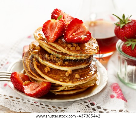 Strawberry pancakes with addition of maple syrup and caramel topping
