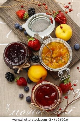 Strawberry, peach and blueberry jams - stock photo