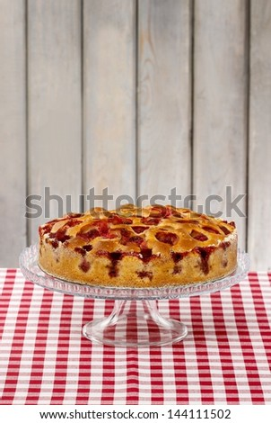 Strawberry pie on cake stand, wooden background - stock photo